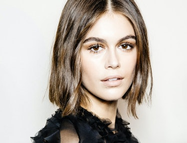 Kaia Gerber wearing a sheer black blouse