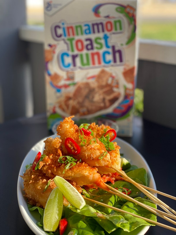 A plate of Cinnamon Toast Crunch tempura shrimp sits on a table in front of a box of Cinnamon Toast Crunch cereal.