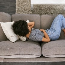 Woman in pain on the sofa.