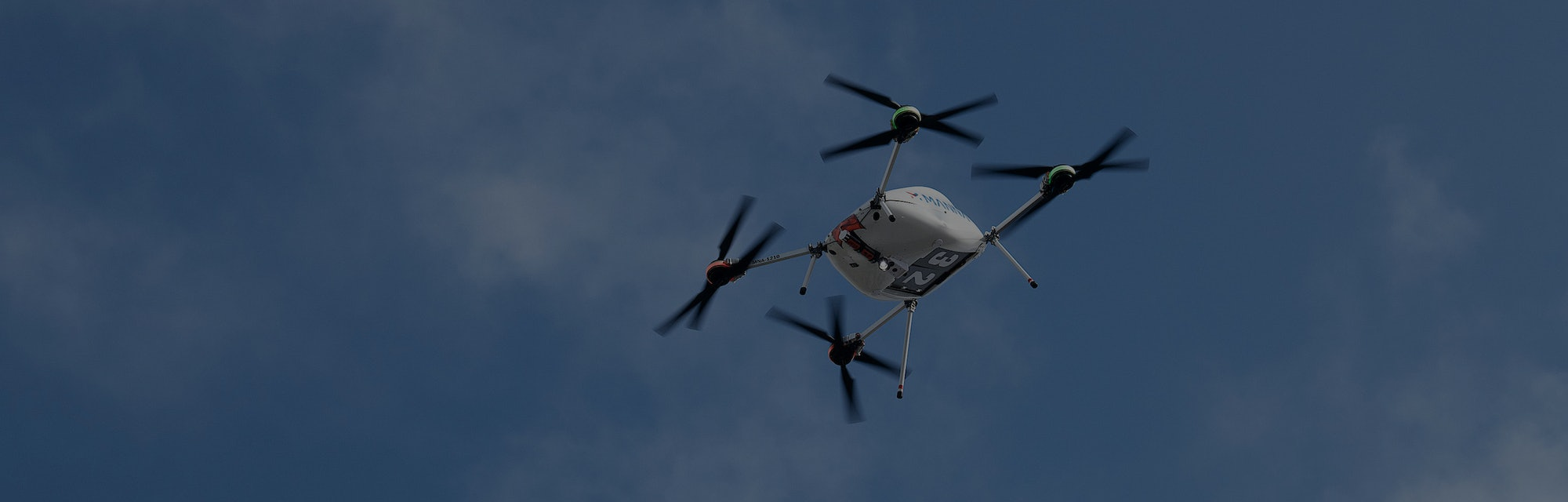A Manna drone carrying a Samsung product is seen hovering in the air.