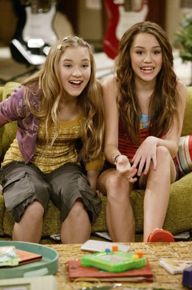 Miley and Lily sit on the couch and react to the TV during an episode of 'Hannah Montana'.