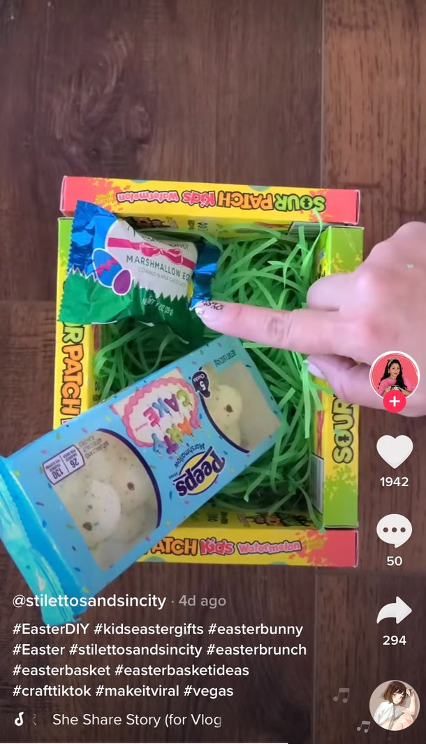 A woman fills up an Easter basket made out of candy boxes.