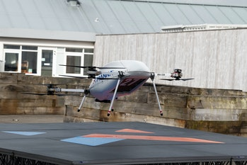 A large sized Manna drone is seen taking off of the ground. This drone is being used to deliver Sams...