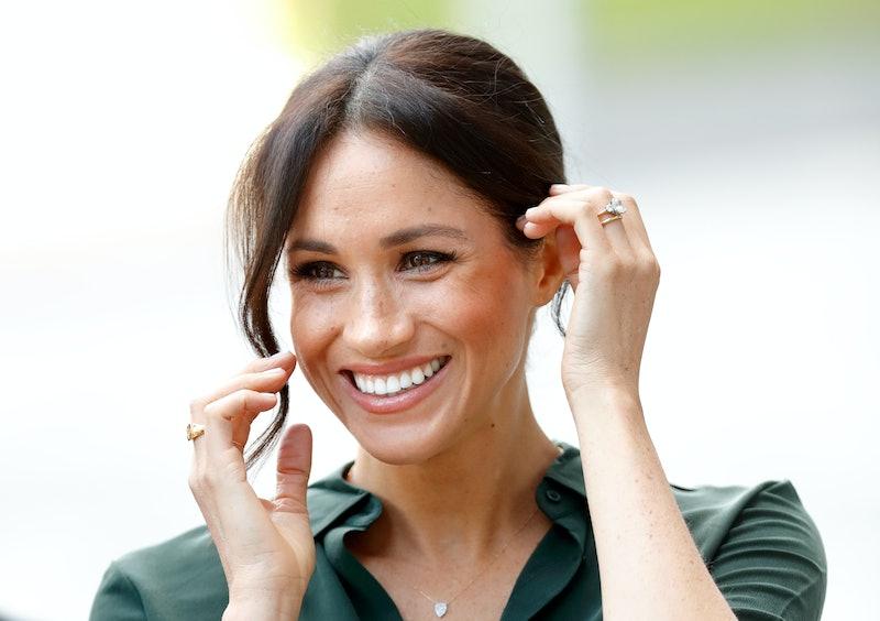 Meghan Markle smiling, wearing very meaningful jewellery