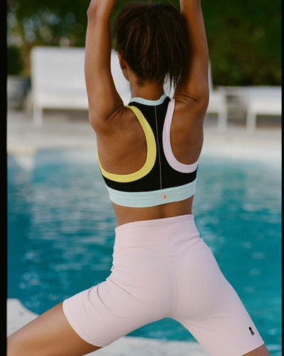 Model wearing bike shorts and sports bra from Solid & Striped Sport collection, now available on Bandier.