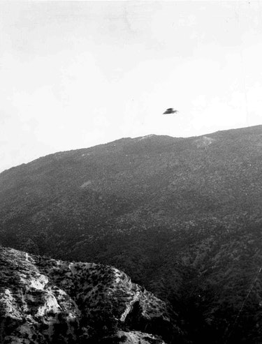 A UFO over a large hill