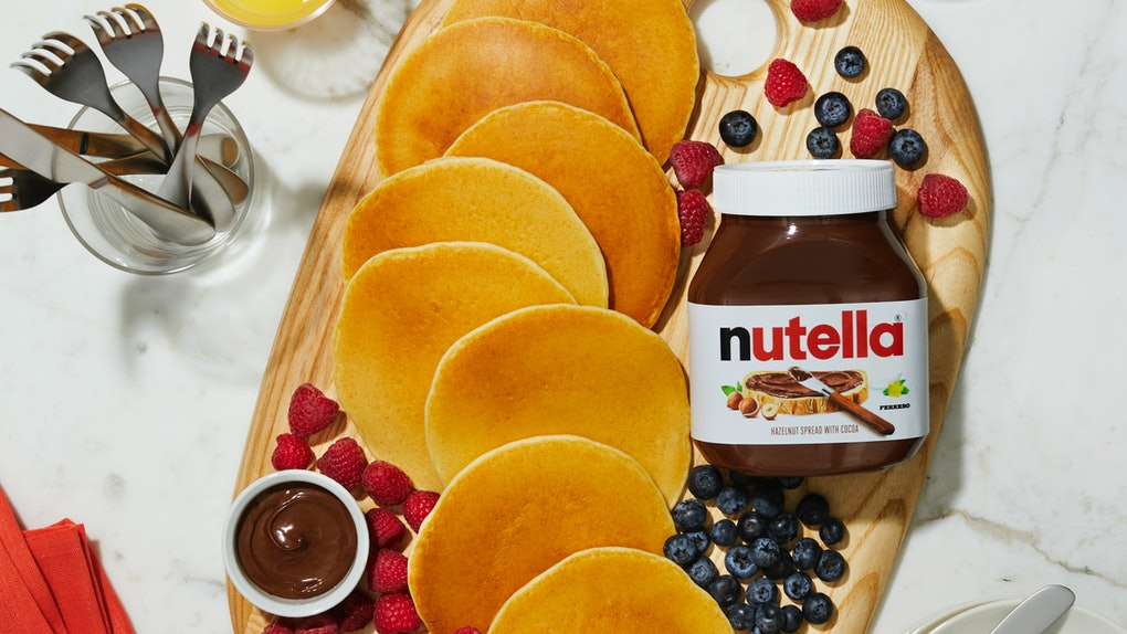 A pancake board is decorating with fruit and Nutella, in support of Nutella and Williams Sonoma's virtual breakfast classes.