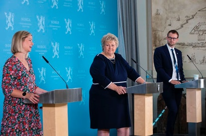 Norwegian Prime Minister Erna Solberg, center, with other government ministers, holds a pandemic pre...