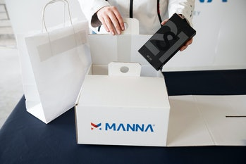 A pair of hands approach a box with the title Manna on it. This box has a Samsung gadget inside.