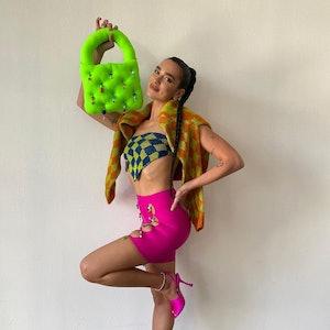 Dua Lipa holding a neon green statement bag.