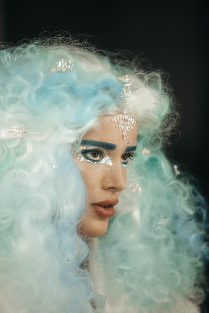 """A profile shot of Bella Thorne filming the """"Phantom"""" music video. She is wearing a curly silver and light blue wig. She has silver eyeliner around her eyes, and is looking off-screen."""