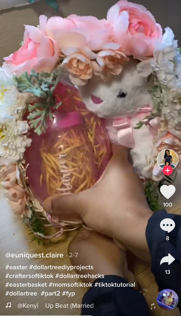 A woman fills up an Easter egg made out of string and fake flowers.