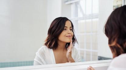 woman looking in her bathroom mirror
