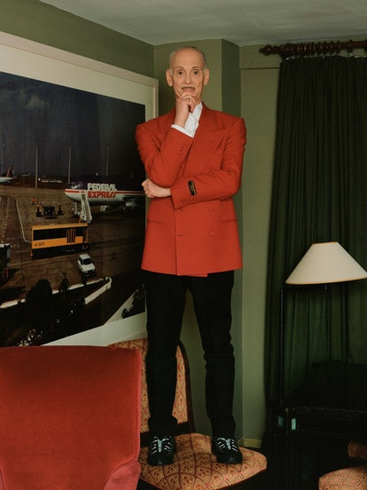 John Waters standing on a chair