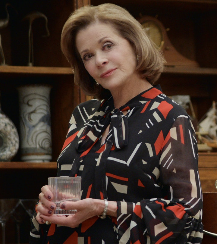 Jessica Walter as Lucille Bluth is wearing a black, red and white dress and holding a rocks glass.