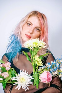 Hayley Williams, co-owner of Good Dye Young, poses with blonde hair that's dyed both pink and blue in spots