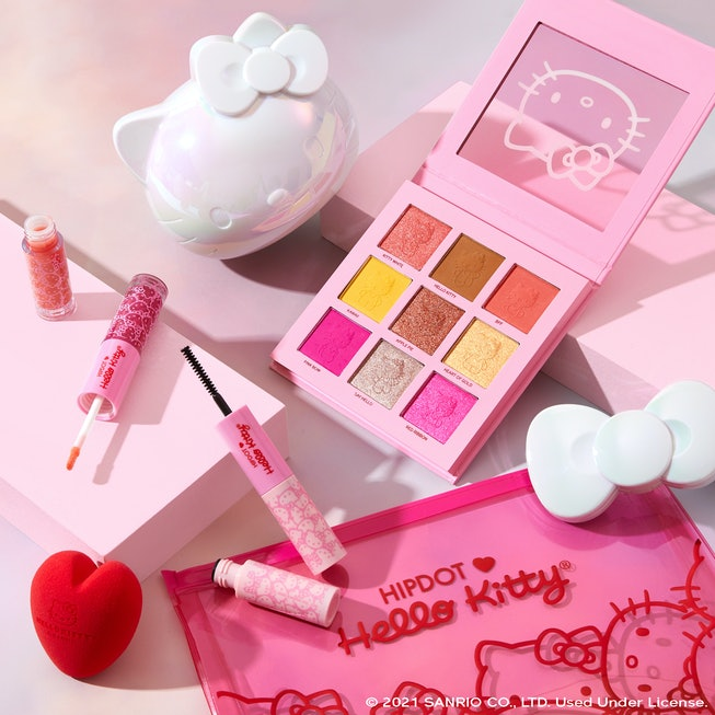 HipDot Hello Kitty products, including an eyeshadow palette and mascara, are laid out on a white background