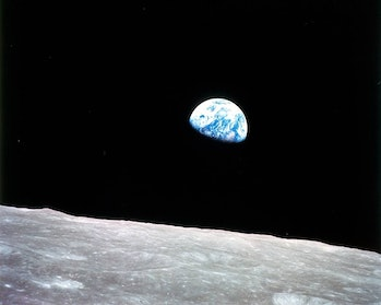 An image of the Earth over the surface of the Moon