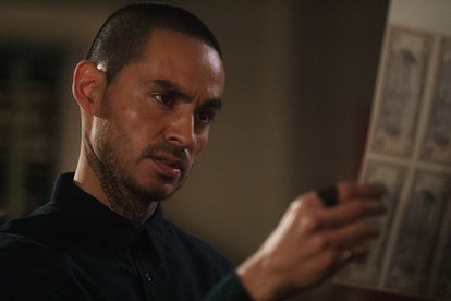 Rio from Good Girls holding a sheet of counterfeit bills in his hands and looking at them.