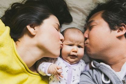 Mom and dad kissing baby as they all snuggle on a bed