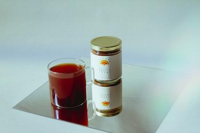 A glass of dark liquid sits next to Rainbo products