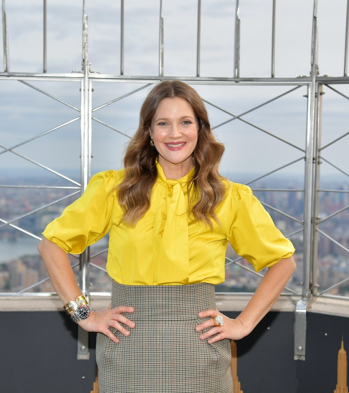 Drew Barrymore, wearing  a bright yellow blouse and a grey pencil skirt, poses at The Empire State Building.