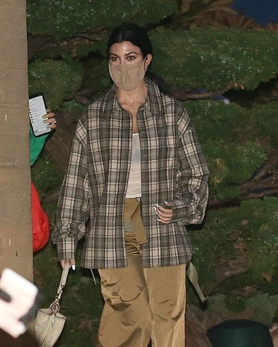 Kourtney Kardashian steps out to dinner at Nobu in a see-through tank top, plaid shirt and shiny beige pants in Malibu.