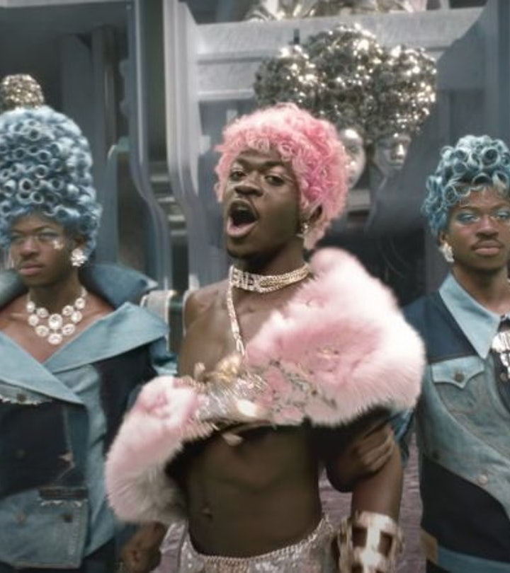 """A screenshot from the """"Montero (Call Me By Your Name)"""" music video, with Lil Nas X shown in triplicate, wearing bring pink and blue wigs."""