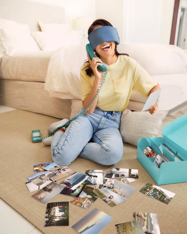 A young woman sits on her living room floor with travel photos while wearing a sleep mask from Away's Travel Well collection.