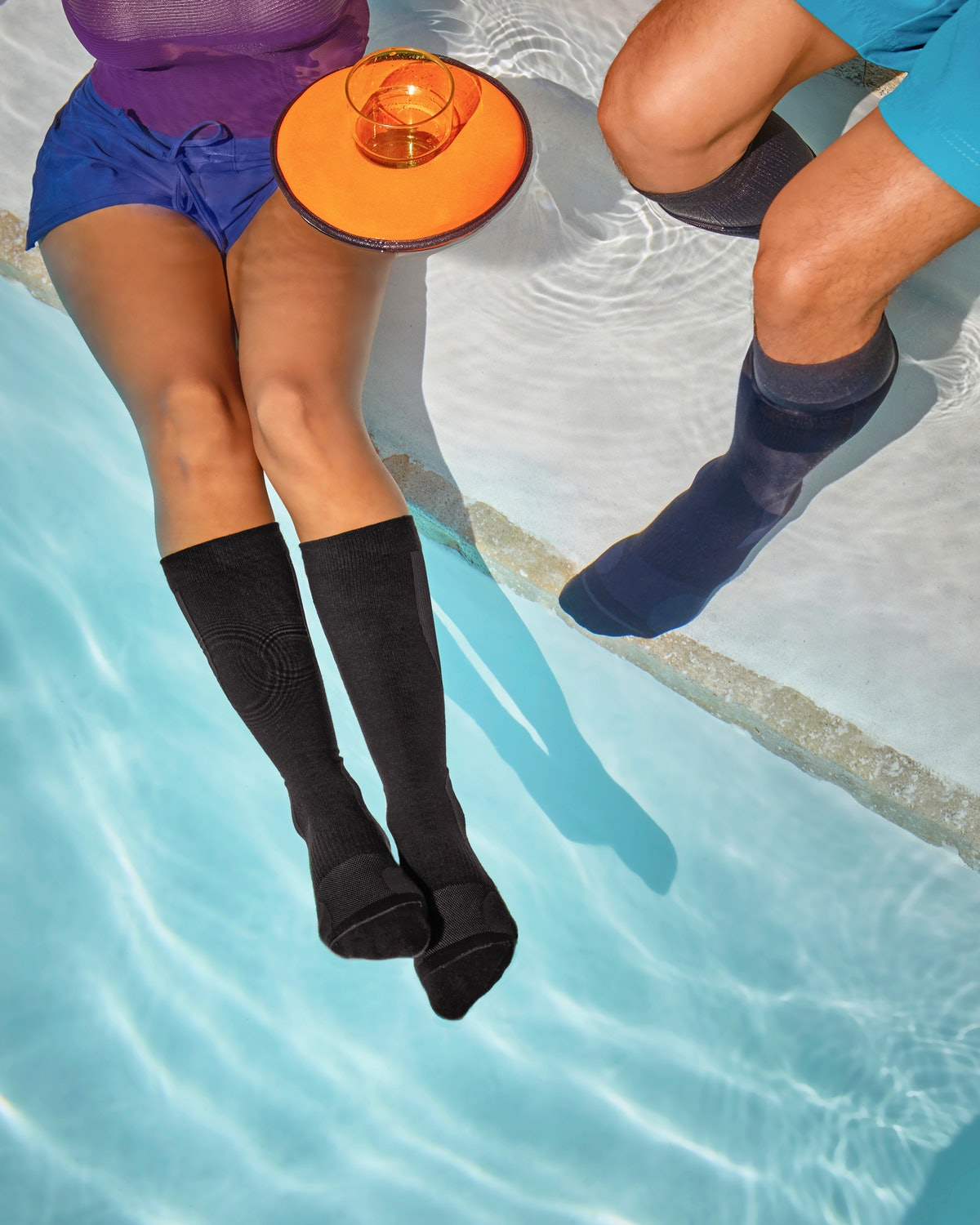 A young couple sits near a pool while wearing compression socks from Away's Travel Well collection.