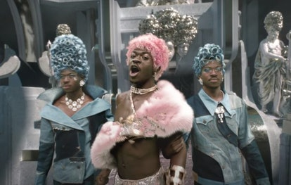 "A still from the ""Montero (Call Me By Your Name)"" music video, with Lil Nas X shown in triplicate, wearing bright pink and blue wigs."
