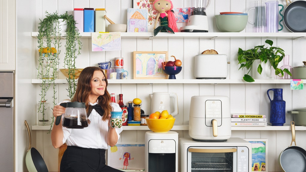 Drew Barrymore sits on a kitchen counter with some Beautiful Kitchenware around her.