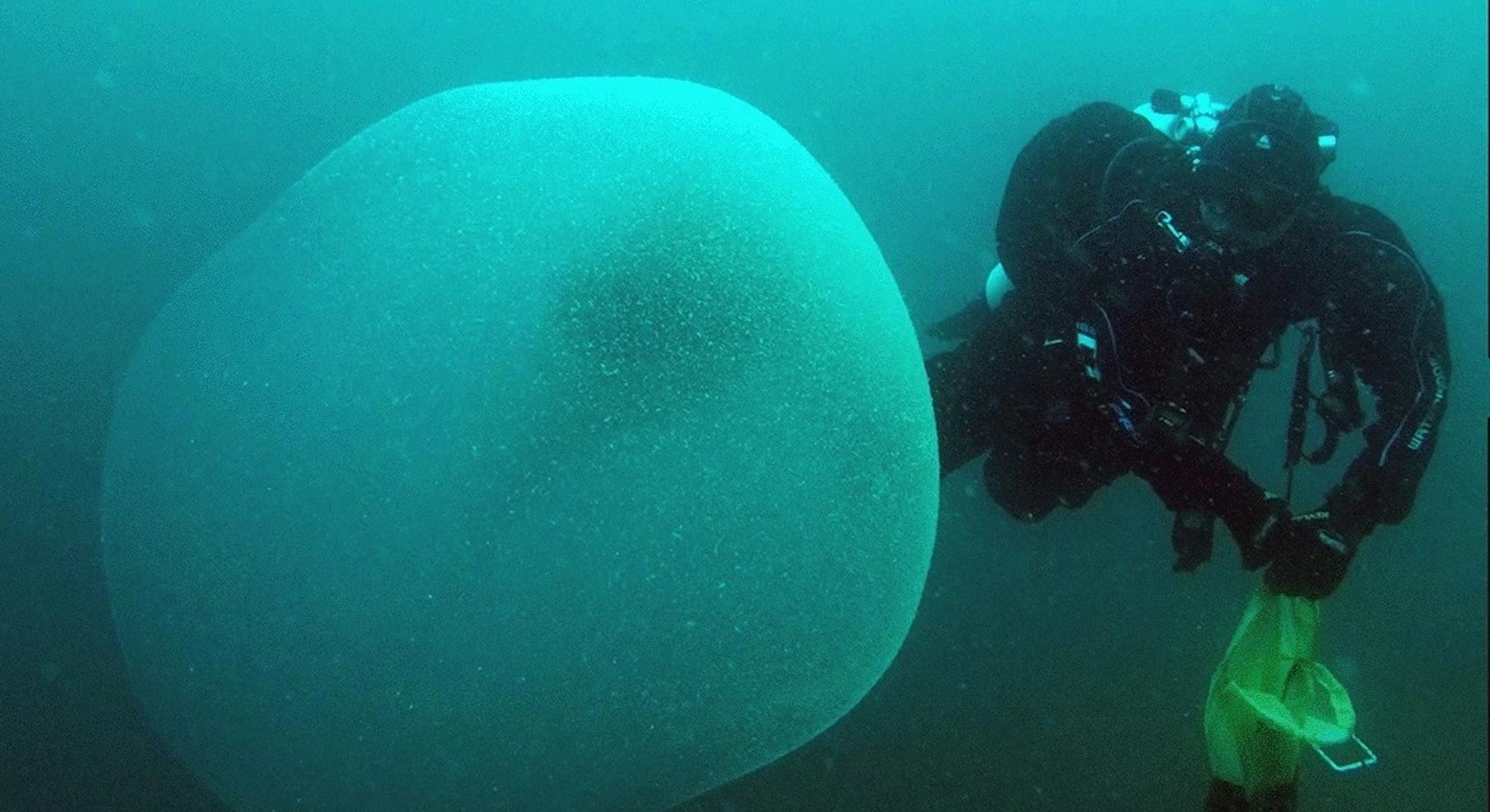diver examines giant sphere underwater