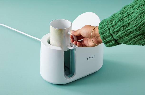 A woman puts a mug into the Cricut Mug Press to make a DIY mug.