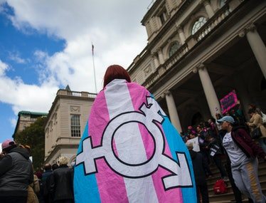A person wearing a flag with the transgender symbol