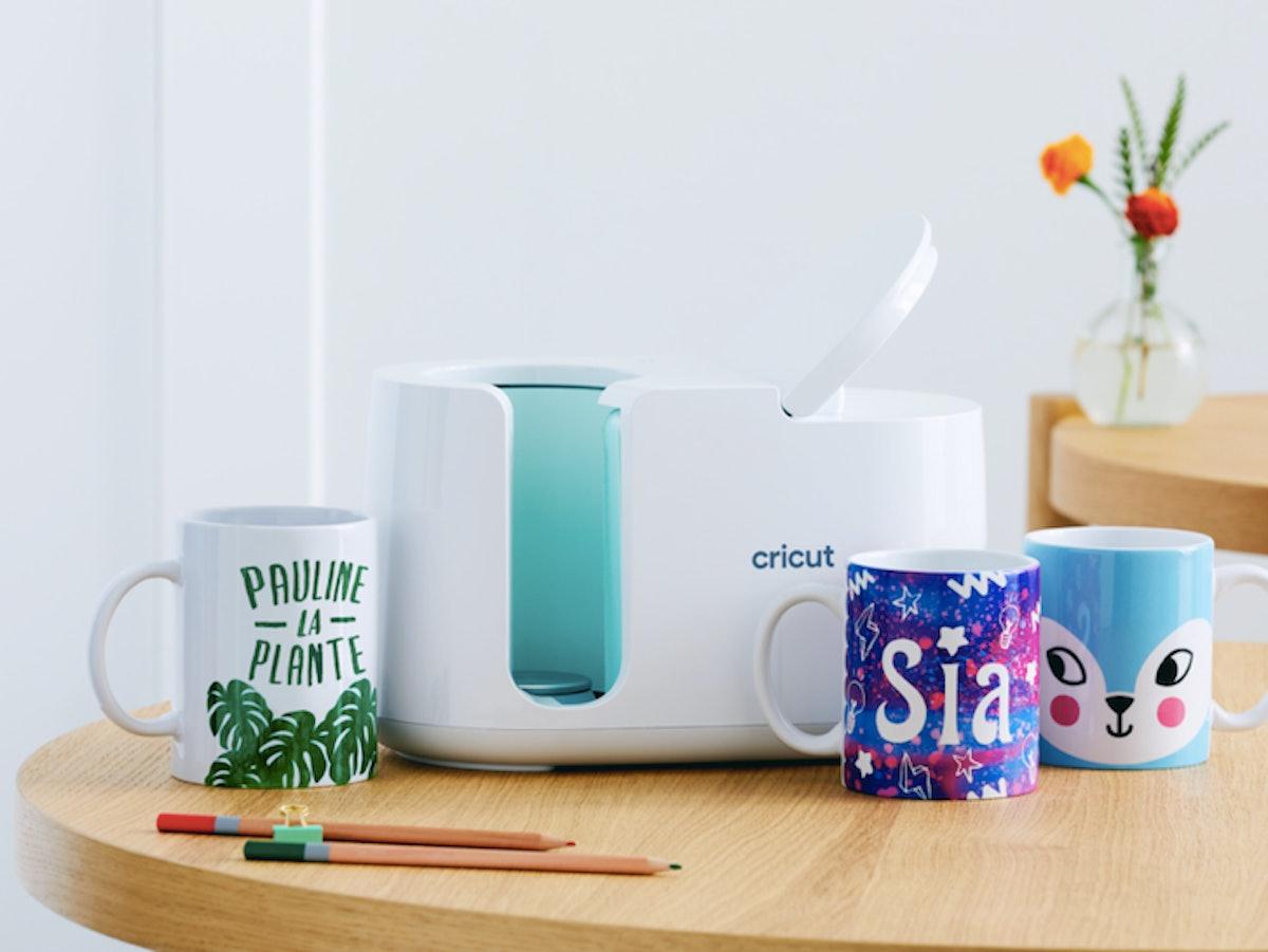 A Cricut Mug Press sits on a table with one-of-a-kind custom DIY mugs.