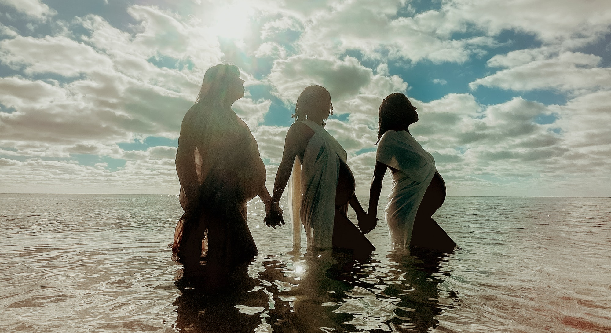 Three pregnant women in the water. Apple partnered with female photographers for an International Women's Day photo series about gender.