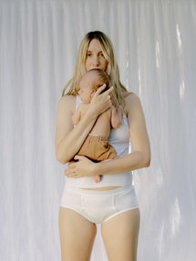 Leah holding her baby, in a tank top and underwear