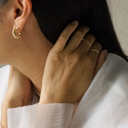Close up of woman wearing pearl hoop earrings and gold rings on her hand