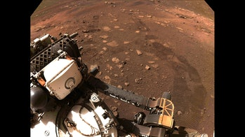 A selfie from the Perseverance rover with tire tracks visible from its first drive.