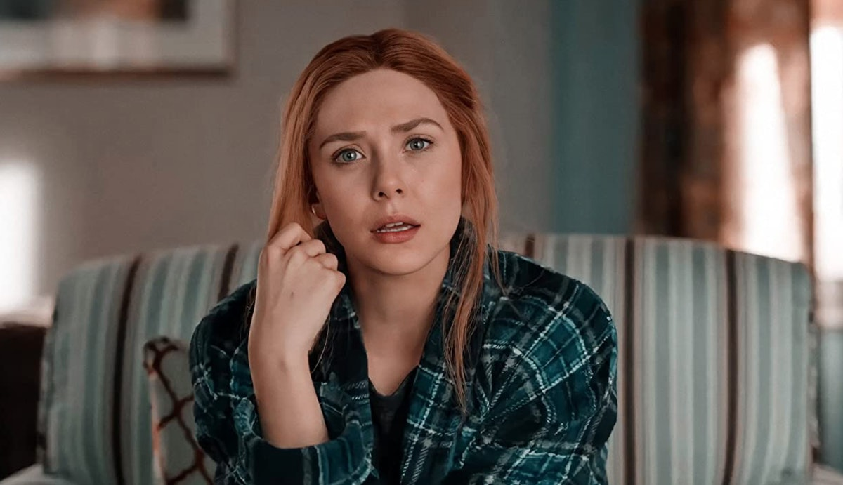 Elizabeth Olsen sits on a couch and looks shocked during an episode of 'WandaVision,' and sports a n...