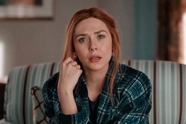 Elizabeth Olsen sits on a couch and looks shocked during an episode of 'WandaVision,' and sports a natural hair and makeup look.