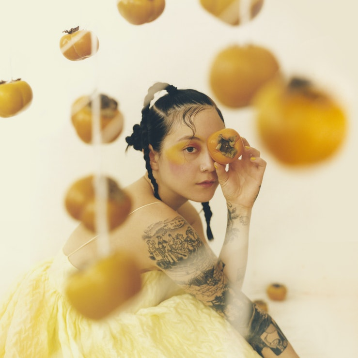 The cover of Japanese Breakfast's new album 'Jubilee.' She is wearing a pale yellow dress, holding a persimmon over her right eye.