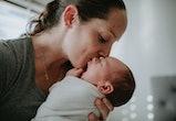 mother kissing swaddled newborn