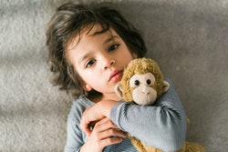 A small child looks up at the viewer, as he snuggles with his stuffed animal monkey on the floor