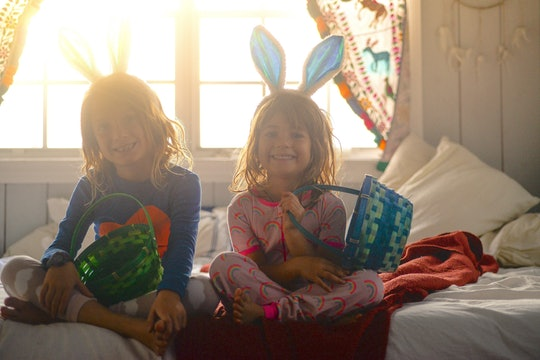 kids sitting on the bed in their easter pajamas, wearing bunny ears