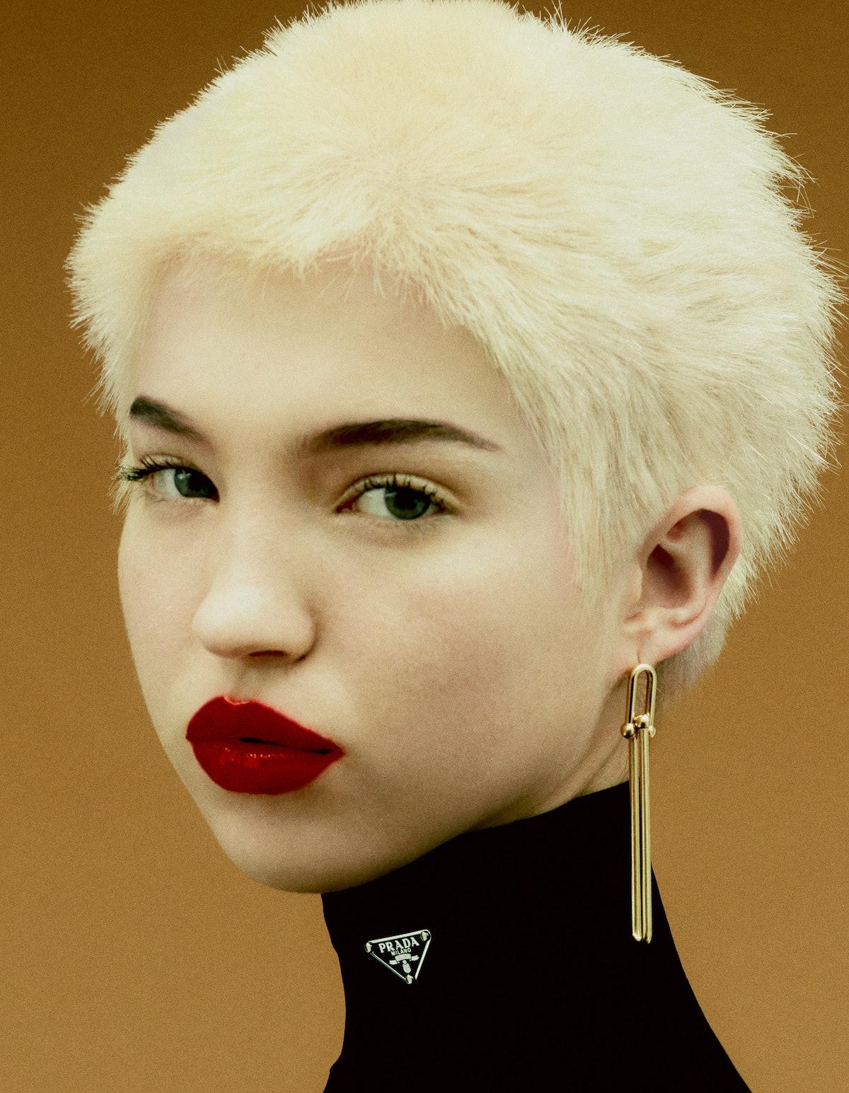 Lila Moss wears a Prada turtleneck; Tiffany & Co. earrings. Rouge Dior Satin Lipstick in #869 Sophisticated.