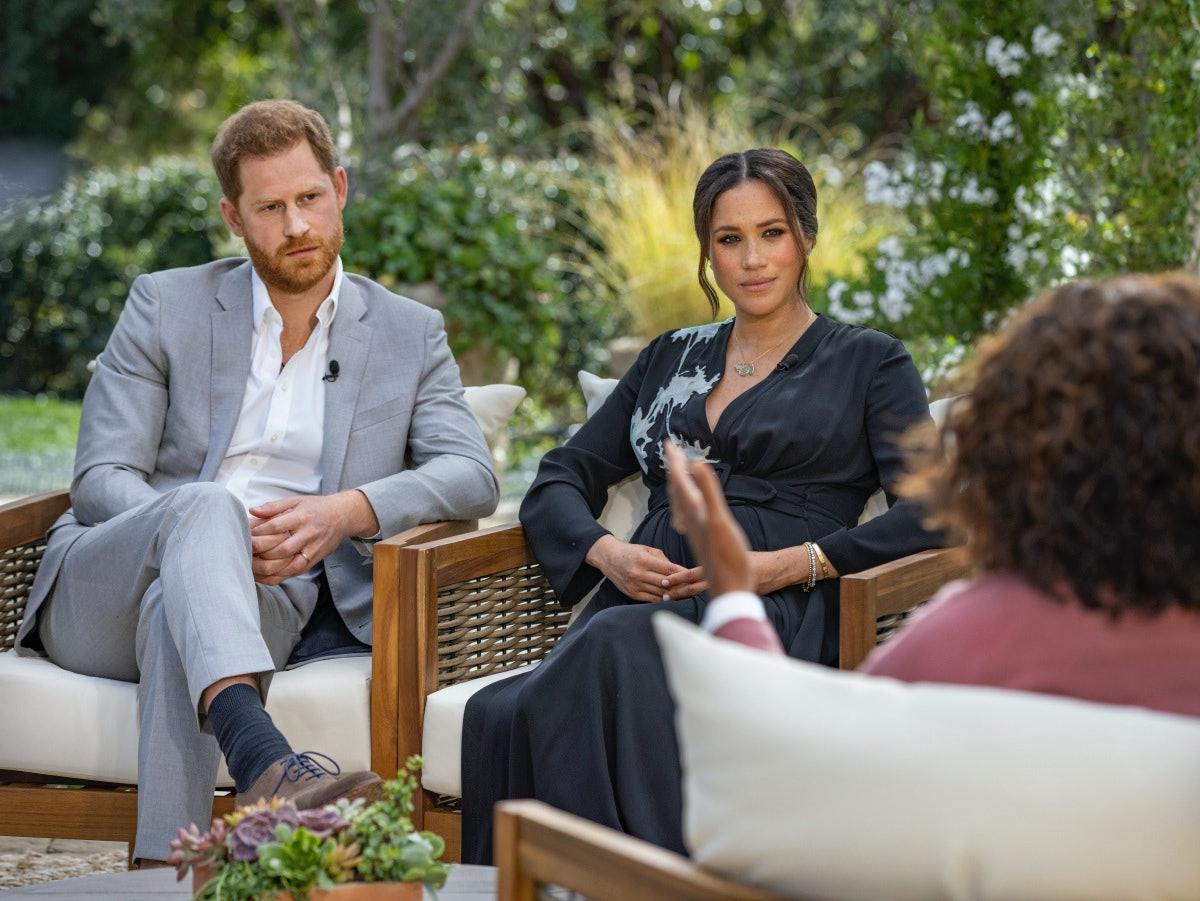 Prince Harry and Meghan Markle listen as Oprah Winfrey asks them a question.