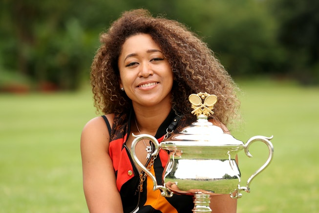 Naomi Osaka seated on grass with trophy