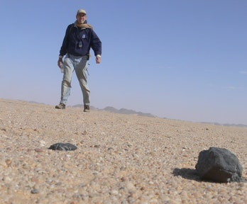 A man in the desert with some rocks in the foreground
